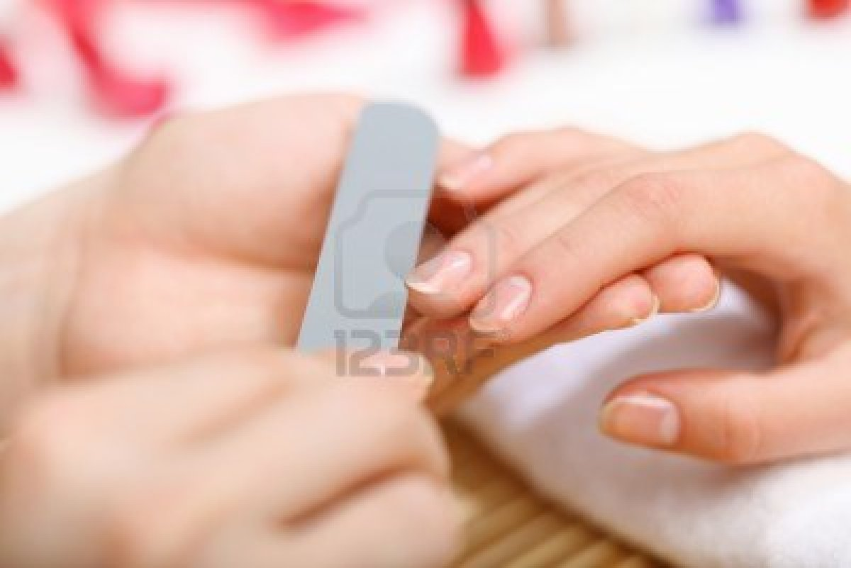 14954870 mujer joven esta haciendo la manicura en un salon de belleza - Manicura semipermanente en casa ...